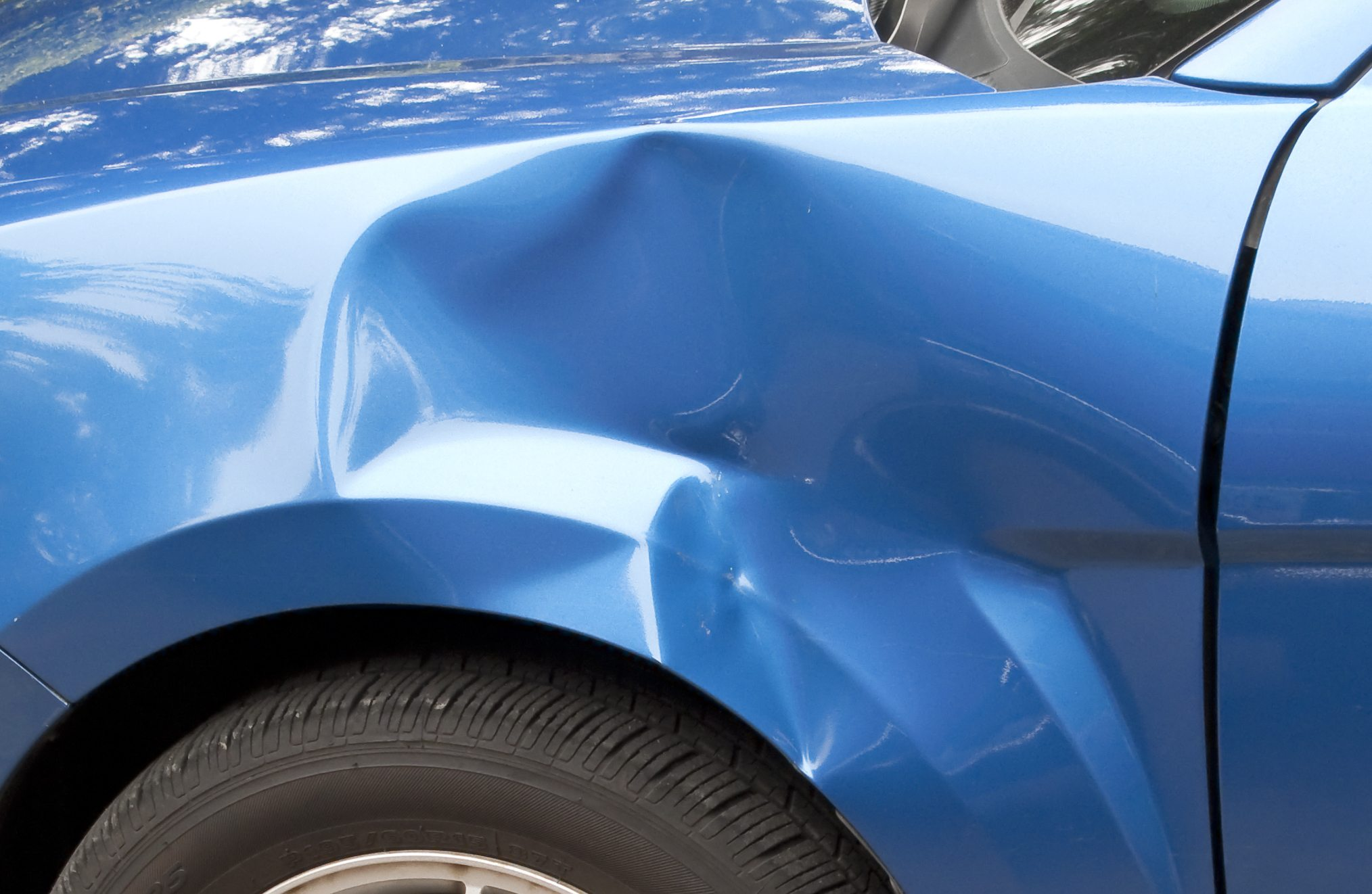 Auto accident leaving a huge dent in the left front quarter panel.